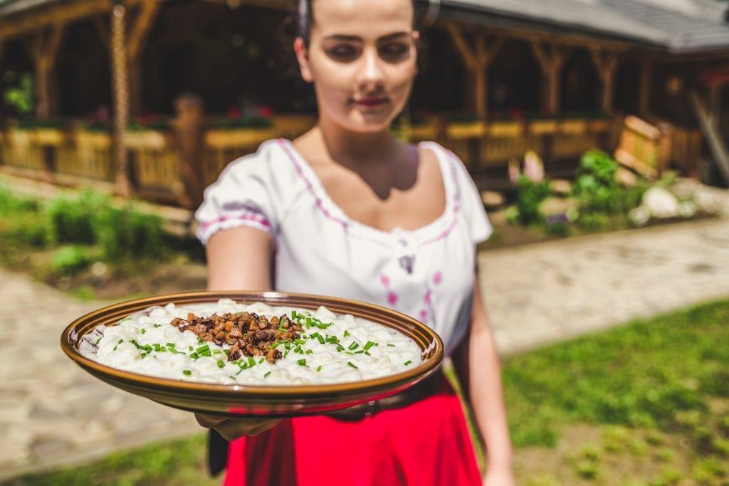 bryndzove-halusky-tanier-zena-kroj-koliba-tradicne-jedlo